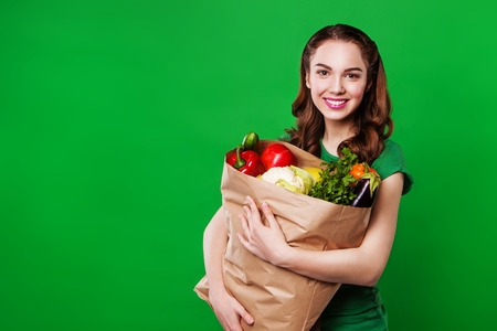 fruits in a basket: Young smiling woman with a grocery shopping bag.