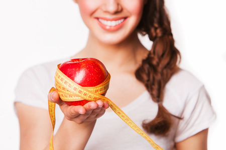 chomp: smiling woman holding an apple and tape measure Stock Photo