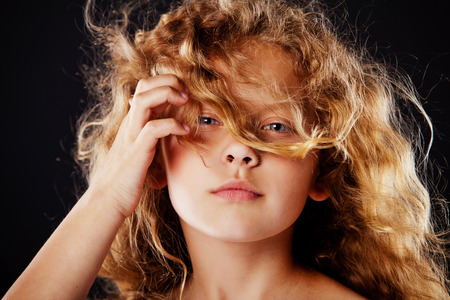 unruly: pretty little girl with windy hair. Fashion photo Stock Photo