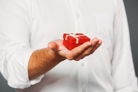 man s: man s hand holding  gift box with a ring