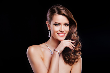 jewel hands: beautiful smiling woman with perfect makeup wearing jewelry