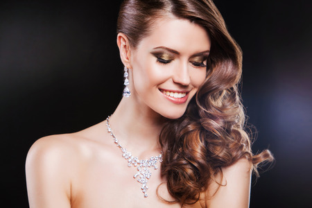 fashion jewellery: beautiful happy brunette woman with luxury accessories.