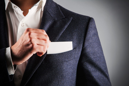 out of business: business man takes out business card from the pocket of business suit, copyspace
