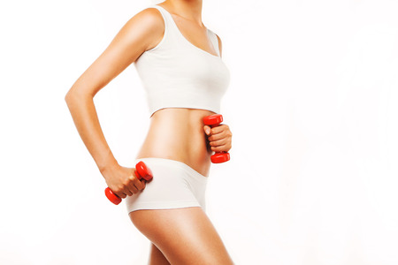 tanned woman: Slim tanned woman s body with red dumbbells on a white background Stock Photo