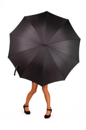 Businesswoman standing behind an umbrella hiding her bust