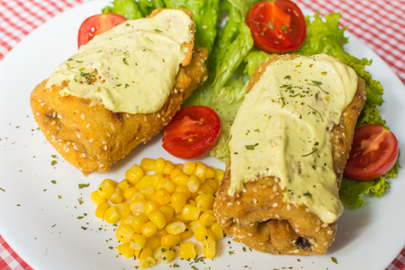 Fried salted pancake with ham in. Lettuce, corn and cherry tomatoes
