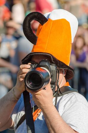 A professional camera photographer shot a carnival report and a festival of humor and satire in Gabrovo, Bulgaria. Snapshot. Photographer with a pink hat that looks like a glass of beer. 写真素材