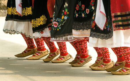 Bulgarian folklore. Girls dancing folk dance. People in traditional costumes dance Bulgarian folk dances. Close-up of female legs with traditional shoes, socks and costumes for Bulgarian folk dances.