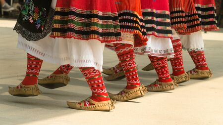 Bulgarian folklore. Girls dancing folk dance. People in traditional costumes dance Bulgarian folk dances. Close-up of female legs with traditional shoes, socks and costumes for Bulgarian folk dances. Stok Fotoğraf - 130708311