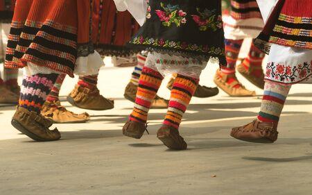 Bulgarian folklore. Girls dancing folk dance. People in traditional costumes dance Bulgarian folk dances. Close-up of female legs with traditional shoes, socks and costumes for Bulgarian folk dances.
