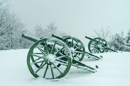 An old metal cannon. The cannon participated in the battles of liberation of Bulgaria in 1877. Winter fog, lots of snow, old cannons covered with snow. Banco de Imagens