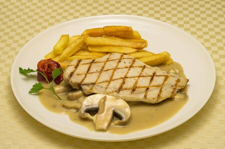 Chicken steak.  Chicken steak with roasted potatoes and mushroom sauce. Chicken steak is served with a piece of mushroom and red roasted pepper for decoration. Place on a white ceramic plate. 写真素材