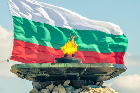 Shipka - Eternal fire. Burns against the backdrop of the National Flag of Bulgaria. The Shipka Freedom Monument, Gabrovo, Bulgaria. Dedicated to the Battle of Shipka Peak (August 1877).