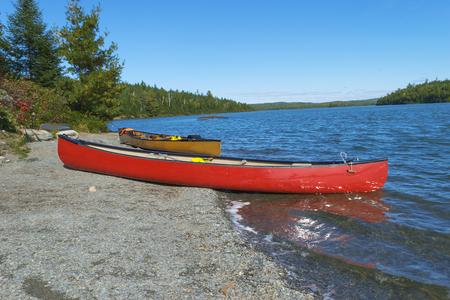Red canoe on rocky shore  of Moose Lake , Boundary Waters Canoe Area,Minnesota, USA