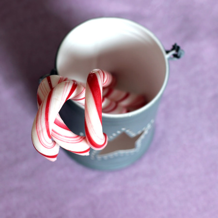 Sweet Christmas candy canes in a light gray cup with a star hole