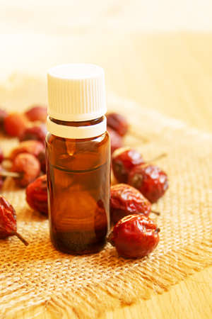 Rosehip seed essential oil in a small bottle. Selective focus.Na