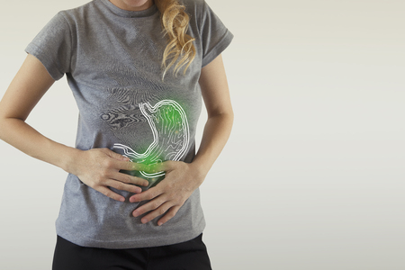 Digital composite of highlighted green  stomach of woman with infection Stock Photo - 120839494