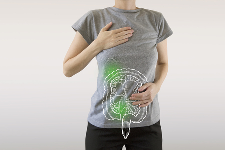 composite image of infected intestine highlighted green on woman`s body  health & disease