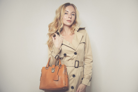 elegant cauccasian woman in beige coat holding brown bag Stock Photo