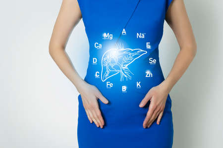 Graphic visualization of healthy human liver with icons of vitamins and minerals. Blurred female figure, positive blue bright color of recovery, health and detox concept. Reklamní fotografie
