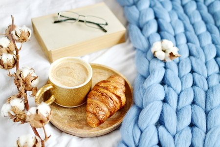 Cup with cappuccino, croissant, blue pastel giant plaid, bedroom, morning concept, cotton flower, book with glasses Фото со стока