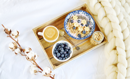 Fresh Breakfast Yogurt with Muesli Banana Berries Chia Seeds Granola Cotton Flower White Giant Knit Blanket Bedroom Healthy Lifestyle Stock Photo