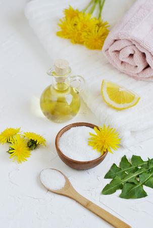Natural ingredients for homemade body salt, sponge with dandelion flowers, lemon, honey and olive oil, SPA concept, white background