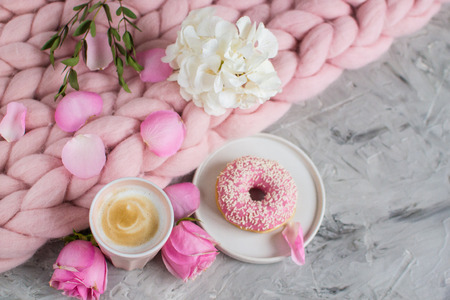 Cup with cappuccino, doughnut, pink pastel giant blanket, flowers, bedroom, morning concept