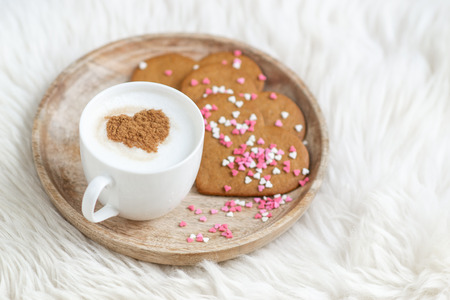 Cappuccino with heart pattern of cinnamon, colorful confetti, valentines day cookies