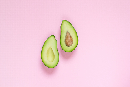 Avocado on pastel pink background, top view, copy space, healthy food concept