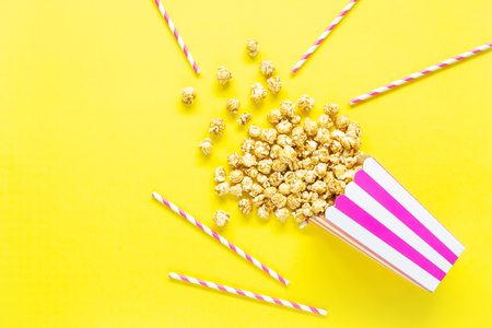 Striped paper cup with popcorn. Top view. Copy space