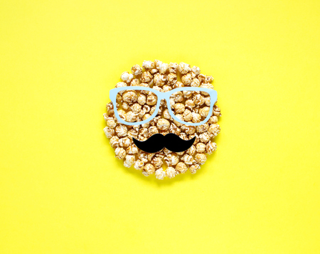 Man head from popcorn on yellow background. Top view. Фото со стока