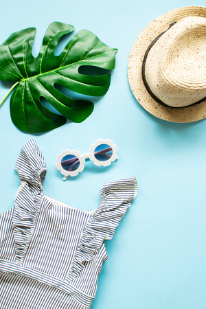 Composition of white modern sunglasses, tropical leaves on blue background. Beach relax. Summer creative concept. Flat Lay. Top view