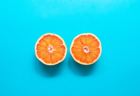 Two red orange grapefruit slices on blue background, flat lay, minimalism, summer creative concept