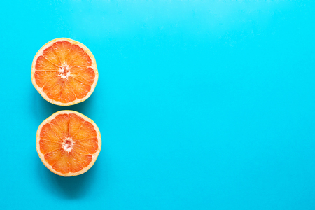 Two red orange grapefruit slices on blue background, flat lay, minimalism, summer creative concept Фото со стока - 123271284