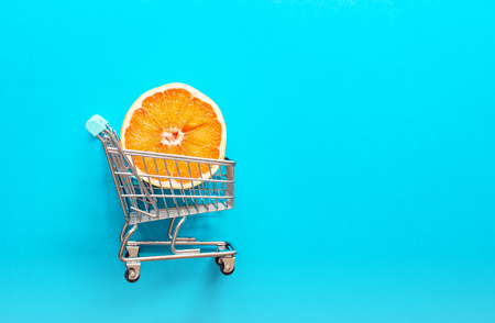 Red orange grapefruit slice in mini trolley on blue background, flat lay, minimalism, summer creative concept