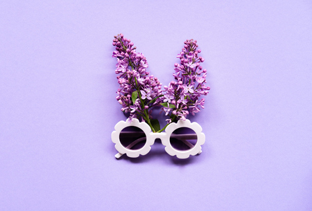 Composition of white modern sunglasses with lilac flowers on purple background. Summer creative concept. Flat Lay. Top view