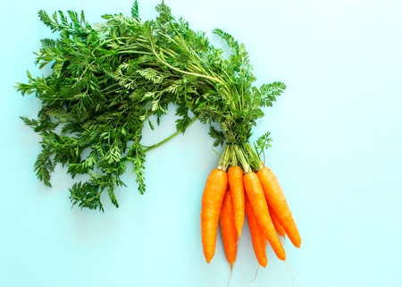 Fresh carrot on blue background, top view, copy space, healthy food Фото со стока