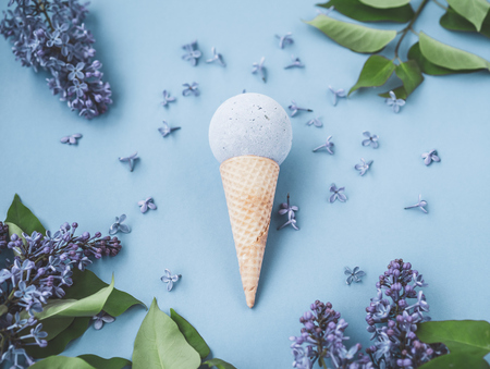Composition of ice cream on a blue background. Bathroom cosmetic accessories. Flat Lay. Top View. Lilac flowers. Toned photo Фото со стока