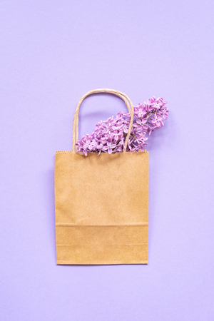 Composition of paper ECO bag with violet lilac flowers. Flat Lay. Top View. Summer creative concept. Copy space