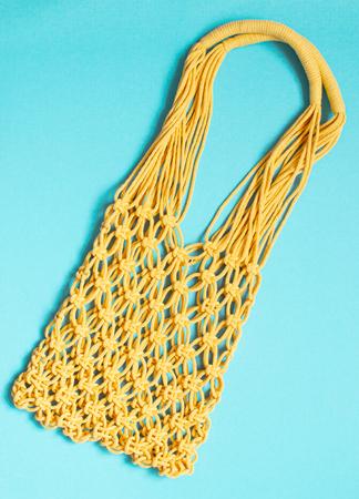 Handmade yellow macrame bag on the blue background, ECO friendly. Modern summer beach concept