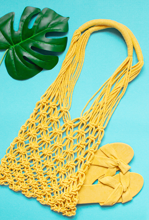 Handmade yellow macrame bag on the blue background, ECO friendly. Modern summer beach concept Фото со стока - 127114965