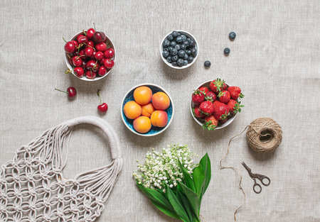 Picnic time. Handmade macrame bag on the linen background, ECO friendly. Strawberries, sweet cherry, blueberries. Modern summer concept