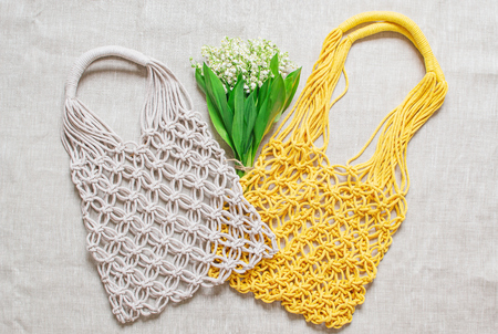 Handmade macrame bag on the linen background, ECO friendly. Embroidery. Modern summer concept. Lily of the valley bouquet