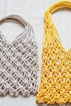 Handmade macrame shopping bags on the linen background, ECO friendly. Embroidery. Modern summer concept