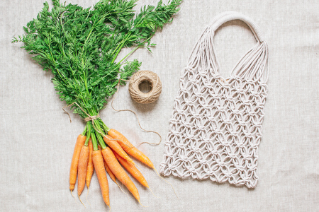 Handmade macrame bag with fresh carrots on the linen background, ECO friendly. Embroidery. Modern summer concept Фото со стока