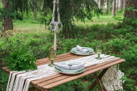 Wedding reception table with macrame tablecloth, decoration on a rustic wooden table Фото со стока - 127115075