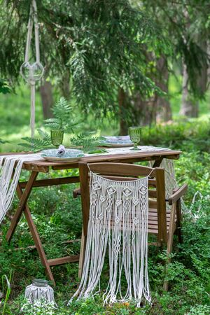 Wedding reception table with macrame tablecloth, decoration on a rustic wooden table Фото со стока - 127115164