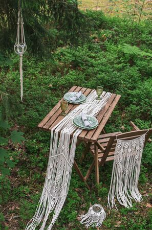Wedding reception table with macrame tablecloth, decoration on a rustic wooden table Фото со стока