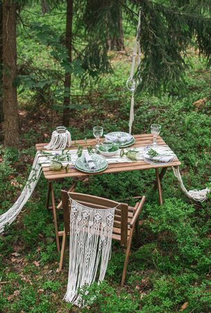 Wedding reception table with macrame tablecloth, decoration on a rustic wooden table Фото со стока - 127115192